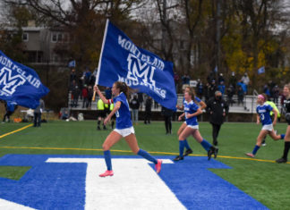MHS girls soccer runs across the field with Mounties flags