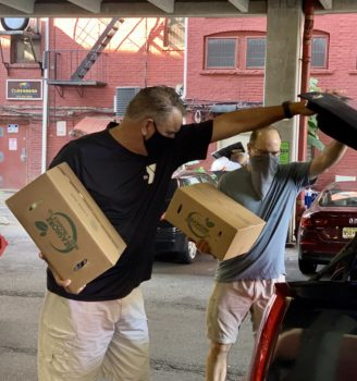 A man takes a box of food out of a trunk. Another man behind him does the same.