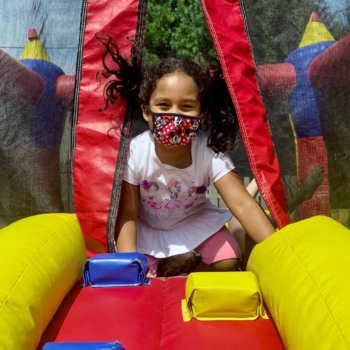 A camper in a bouncy house wears a mask.