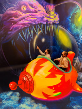 Two people pose in a space-themed mural.