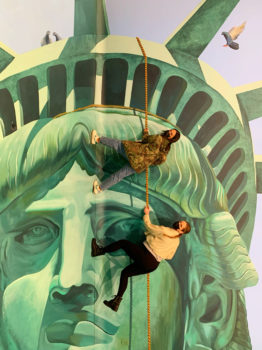 Two people pose in the Statue of Liberty mural.