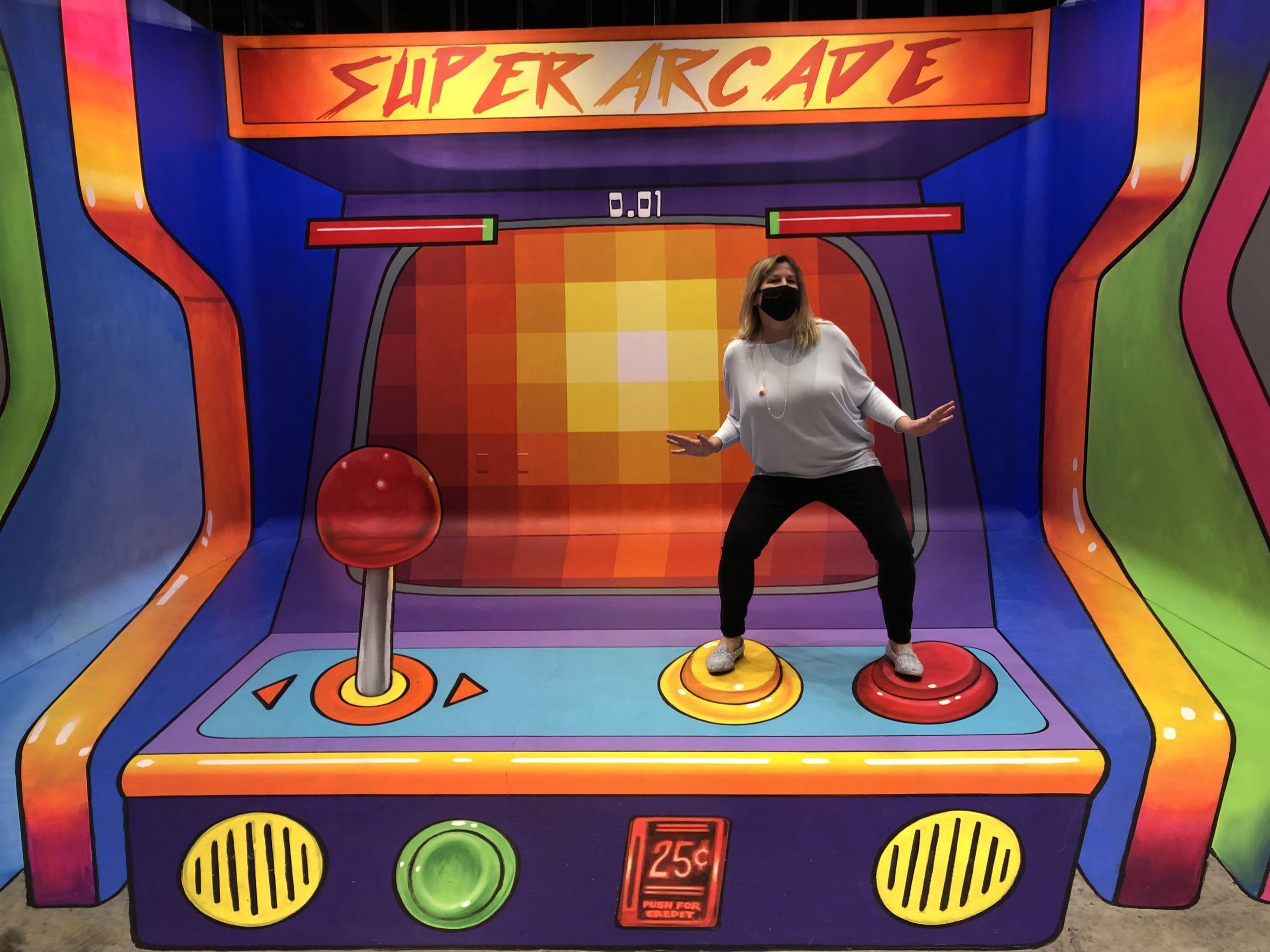 A person poses in the arcade game mural
