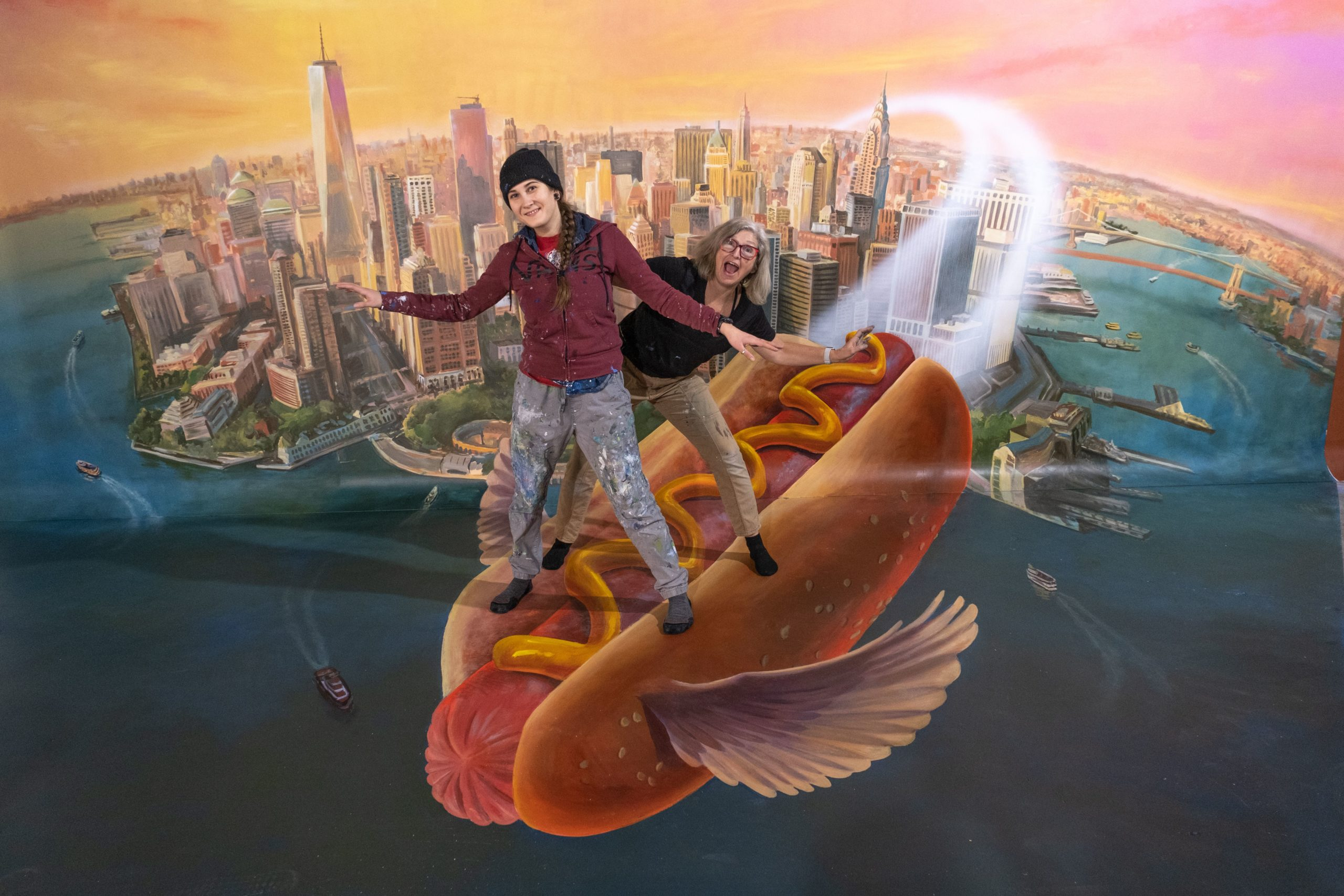 Two people pose in the magic hot dog mural.
